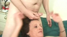 Horny granny grabs two thick pricks and works with her mouth