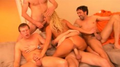 Blonde and brunette nymphos take on a gang of hard cocks on the couch